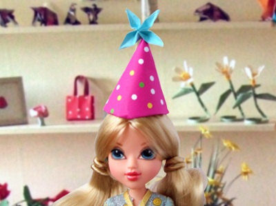 doll with an origami party hat on her head