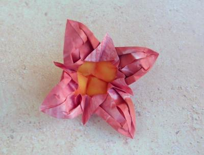 pink origami flower with a yellow center