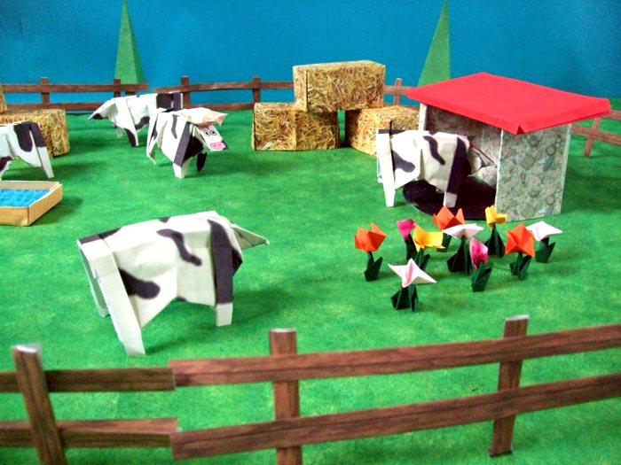 origami cows in a large scenery