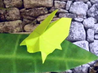 sticky note origami bug on a large leaf